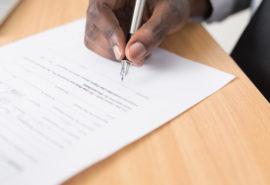 A man signing a contact